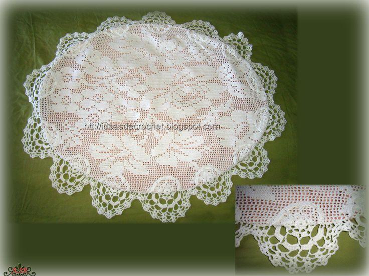 Cojín blanco ovalado a punto de red o filet con diseño de flores.