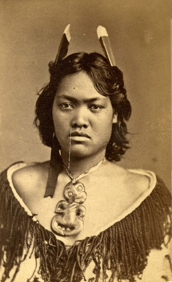 New Zealand | Maori girl; wearing Hei Tiki (neck pendant); huia feathers in her hair, ear ornament of ribbon, and korowai (tag cloak) | Late 19th century | Photographed by Foy Brothers