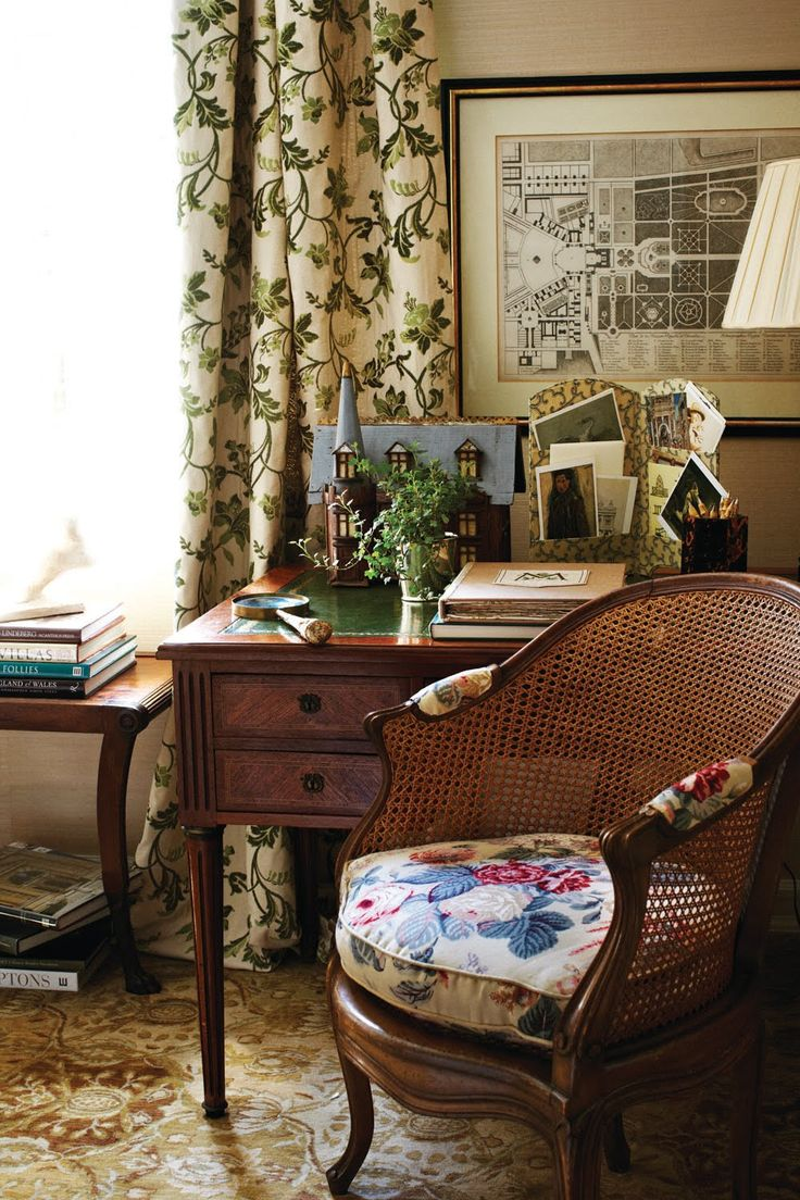 A winding vine fabric, Violet in Ivy at the window and Claire printed floral in Red Eden on the seat cushion at a desk vignette.