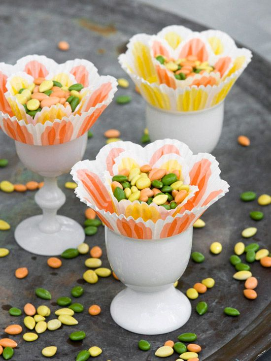 Flower Easter Cups ~  Form a flowerlike favor by nesting a mini paper baking cup inside a standard-size one. Perch both on an egg cup and fill with an Easter treat. For a place card, prop a tag between the liners {courtesy of BHG}