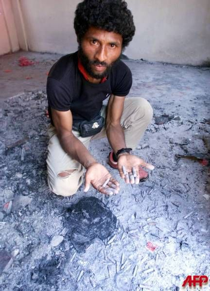 SUAI, EAST TIMOR, 16-OCT-1999: Eliseu Gusmao shows spent bullet shells scattered inside the burned Suai church compound October 16 1999 in East TImor. Gusmao, an eyewitness in the massacre where a Roman Catholic priest was hacked to death, said about 200 people were killed allegedly by militias and Indonesian soldiers during the September 6 attack on the church compound which housed East Timorese seeking refuge from militia violence. [AFP Photo]