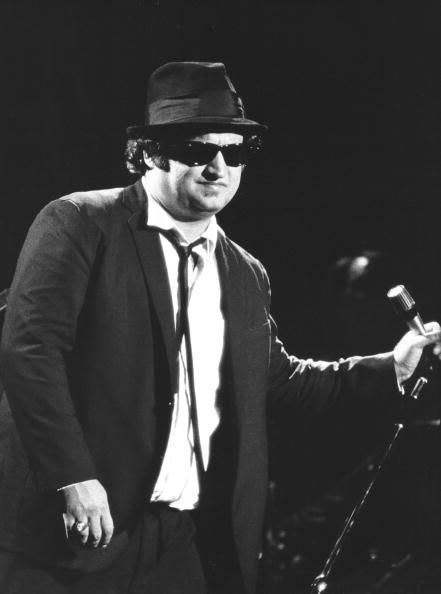 """John Belushi (January 24, 1949 – March 5, 1982) was an Albanian-American comedian, actor, and musician. He is best known for his """"intense energy and raucous attitude""""which he displayed as one of the original cast members of the NBC sketch comedy show Saturday Night Live, in his role in the 1978 film Animal House and in his recordings and performances as one of The Blues Brothers."""