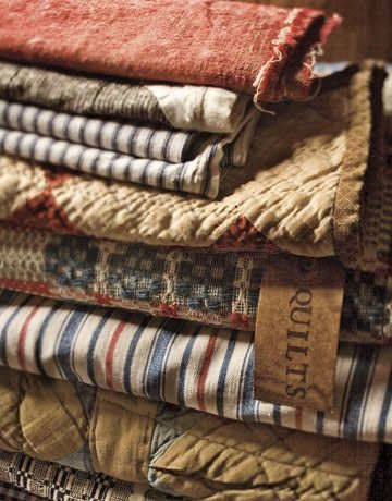 antique ticking, old coverlet, and old quilts