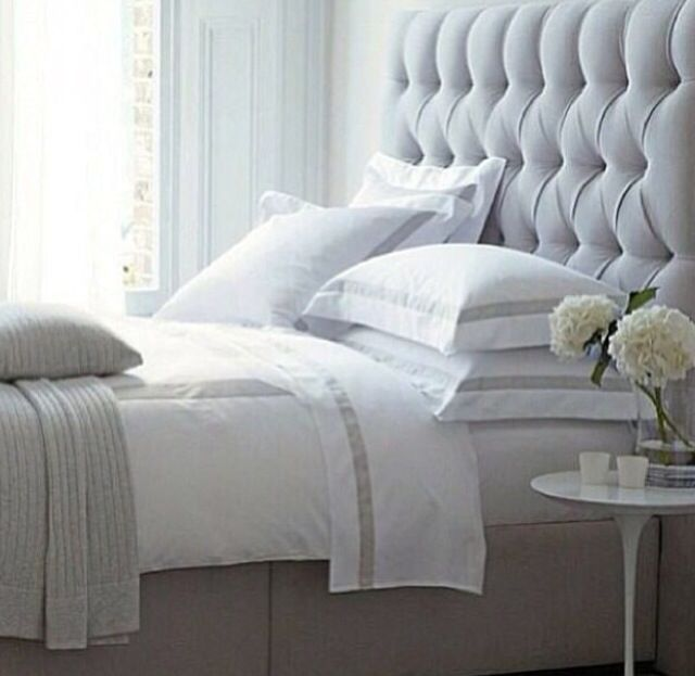 Grey upholstered headboard and white bedding