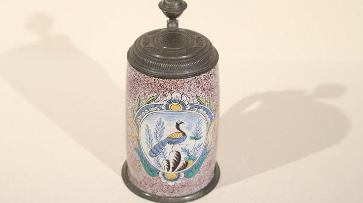Der prunkvolle Bierseidel (Fayence)ist vermutlich um 1800 im bayerischen Ansbach (Fabrik gegründet 1708/10) entstanden. Die Zinnmontur ist mit einer Münze verziert. Der Wert liegt bei etwa 600 bis 800 Euro.