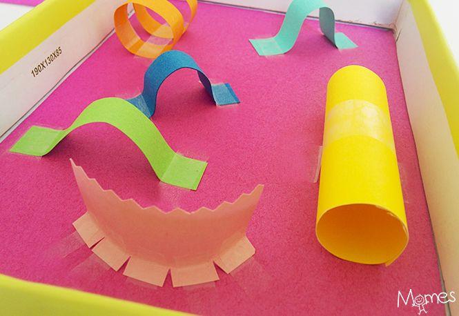 C'est fou comme avec trois fois rien, on peut fabriquer des jouets rigolos ! La preuve avec ce mini-circuit à bille réalisé avec un couvercle de boîte et du papier.