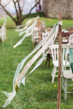 rustikale Naturholzstäbe mit wehenden Bändern in pastellen Farbtönen als Markierung/Deko für jede Sitzreihe