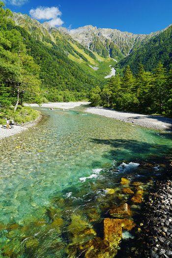 梓川は、標高1500メートルの高原、上高地の中心部をとうとうと流れる清流です。透き通る水はエメラルドグリーンに輝き、川底の石が見えるほどの美しさです。