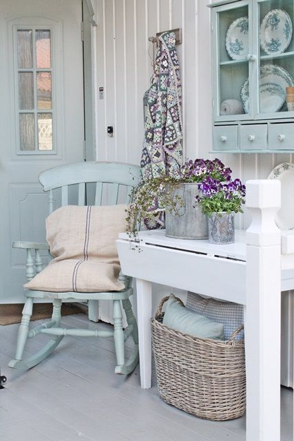 A pretty and welcoming front porch in Norway, done in soft shades of blue green and white with a pop of purple. What a fun place for a granny square throw.