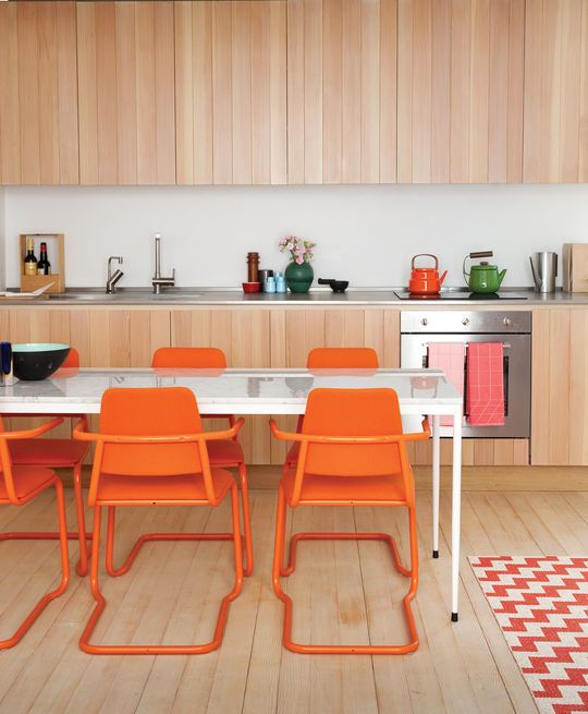In this pint-sizecustom-built London guesthouse kitchen designed by Studiomama, lustrous vertically clad cabinetry achieves additional depth with the addition of the chairs, which were picked up for $15 each at a local market and powder coated in bright orange. Photo byBen Anders.  Photo by Ben Anders.