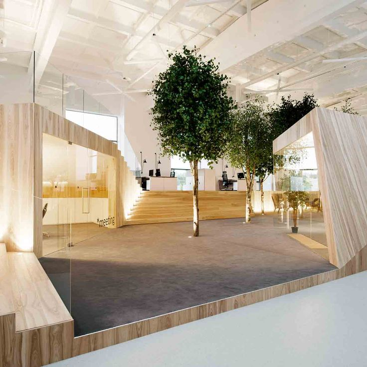 "KAMP Arhitektid has installed angular wooden rooms and trees inside a former factory, to create an office modelled on a ""bright summer forest""."