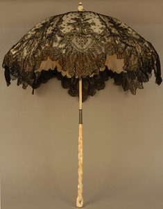 FOLDING CHANTILLY LACE PARASOL CARVED IVORY HANDLE, 1870's. Handle and finial carved in a chain link and rope pattern, black lace canopy lined in cream silk with scalloped edge and fringed band.