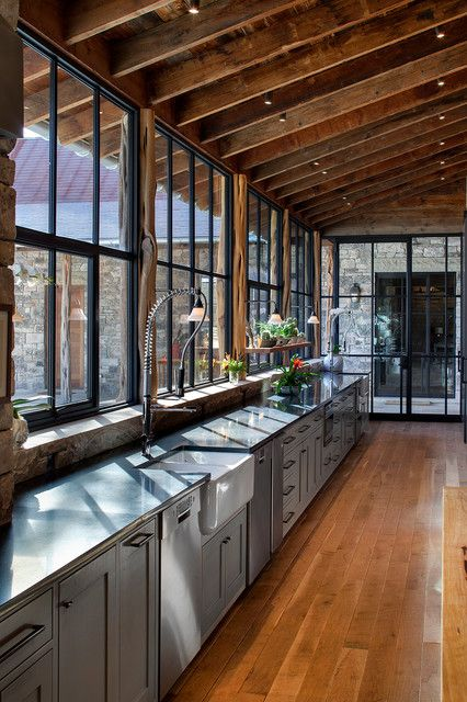 Design ideas for a rustic galley kitchen in Austin with a farmhouse sink, gray cabinets, medium tone hardwood floors, shaker cabinets, stainless steel appliances and an island.