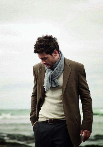 Creamy sweater, grey flannel trousers, brown suit coat, grey scarf.