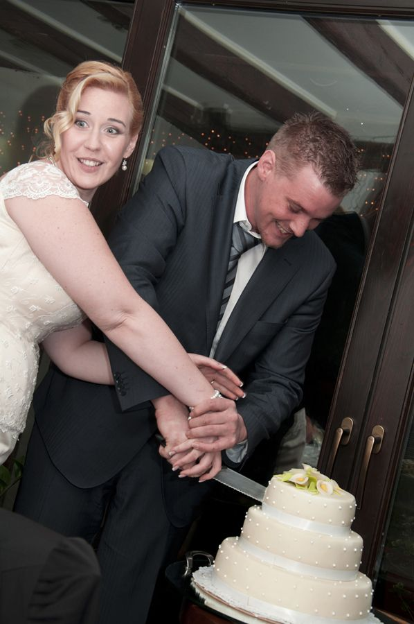 groom and bride cutting cake