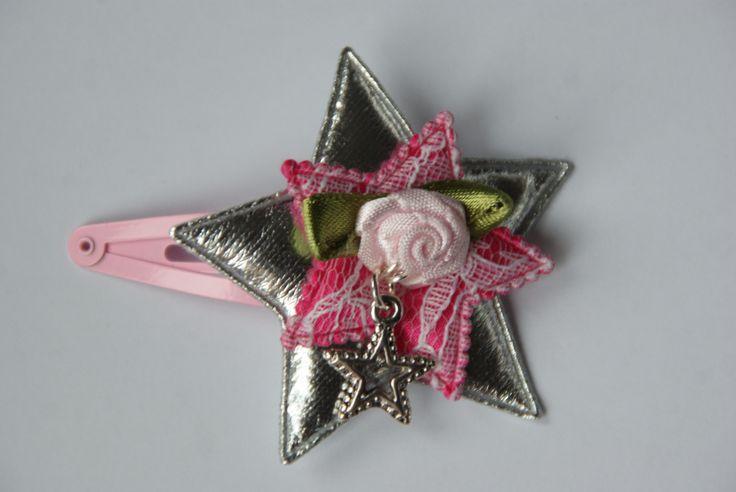Mooie knip met een zilveren ster met daarop een roze ster met wit kant. Daarboven op zit een bloem met een ster als bedel.Door een nieuw systeem is het knipje zo te draaien dat het steeds mooi in de haren zit aan welke kant je de knip ook draagt. www.lotenlynn.nl https://www.facebook.com/lotenlynnlifestyle