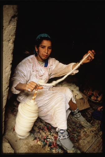 A Berber girl spins yarn on a spindle.  Location:	Atlas Mountains, Morocco.