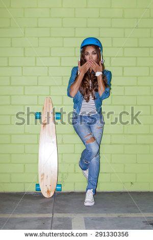 молодая красивая длинноволосая брюнетка девушка в синем шлеме с деревянной Longboard скейтборд кокетливо отправки поцелуй воздуха около зеленой кирпичной стене