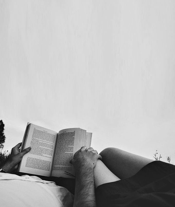 The romance of reading books in bed with your partner.