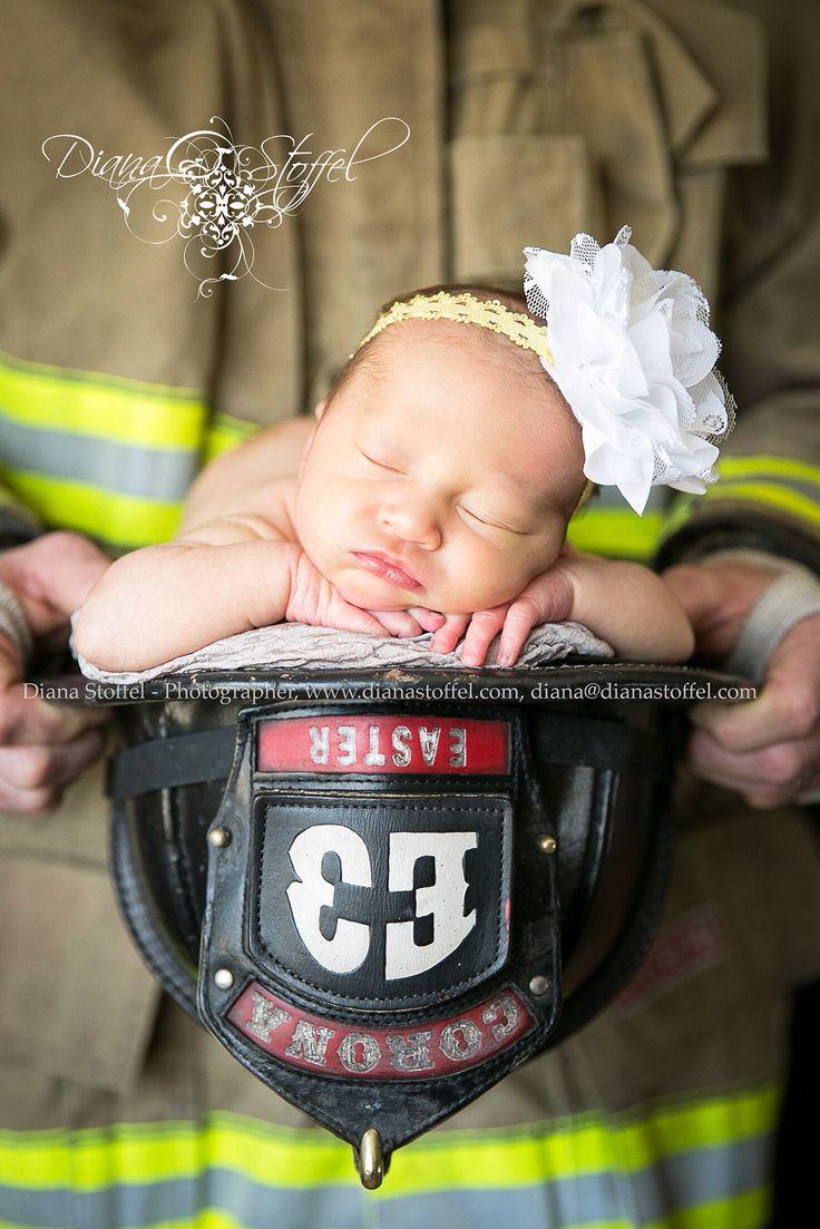 Newborn baby girl pose in firefighter helmet.  Southern California newborn photographer.