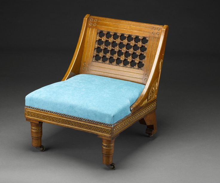 Chair of mahogany, with incised, gilded decoration of geometric and stylised botanical forms in the Aesthetic Egyptian Revival style. Re-upholstered in blue velvet in 2014. Designed by Christopher Dresser, Manufactured by Chubb & Sons or Thomas Knight and retailed by The Art Furnisher's Alliance. British, c. 1880.