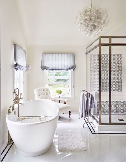The bright, white master bath of Alec and Hilaria Baldwin's East Hampton home features Spanish-inspired blue and white tile from Stone Source, a bubble chandelier from Home Nature, and an elegant freestanding tub.
