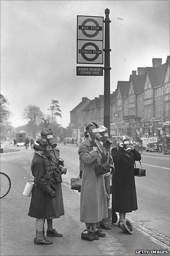 Passengers at a bus stop in Esher wearing their gas masks during a gas test in which tear gas was used.