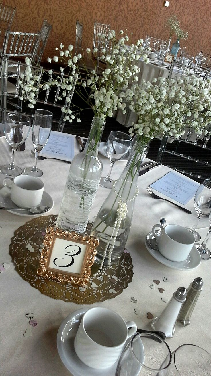 wine bottles, babies breath and pearl centerpieces for a vintage themed wedding; design & décor by Davis Floral Creations