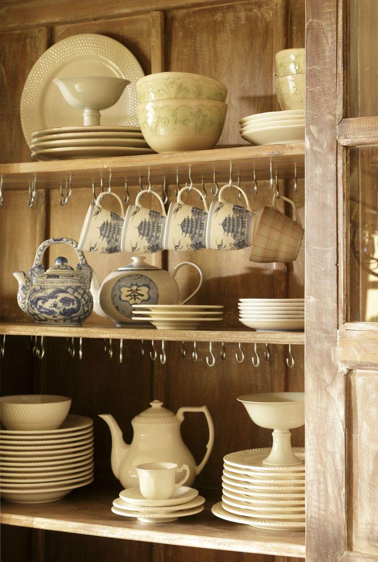 Interior de vajillero con estantes con platos, tazas, teteras y boles de cerámica, con ganchos para colgar tazas