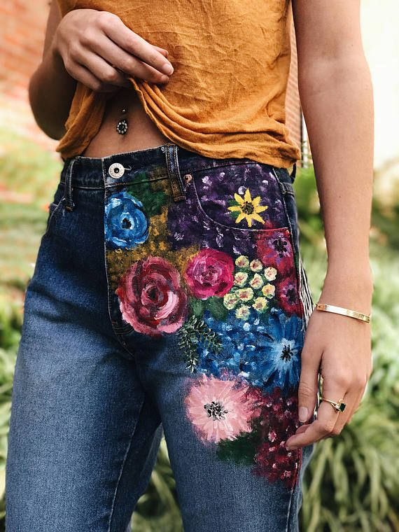 Hand painted boot cut jeans. Multi-colored floral paintings on left thigh, flames around right ankle, and a black and white portrait on the left side/back.
