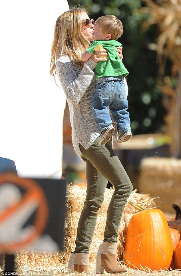 Her little pumpkin: The doting mother lifts her son up as he decides he has found a pumpkin