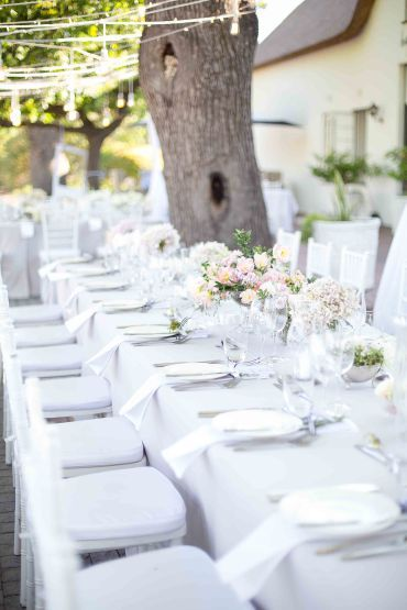 Outside wedding, grey, white and black ribbon, pink, white and green flowers.