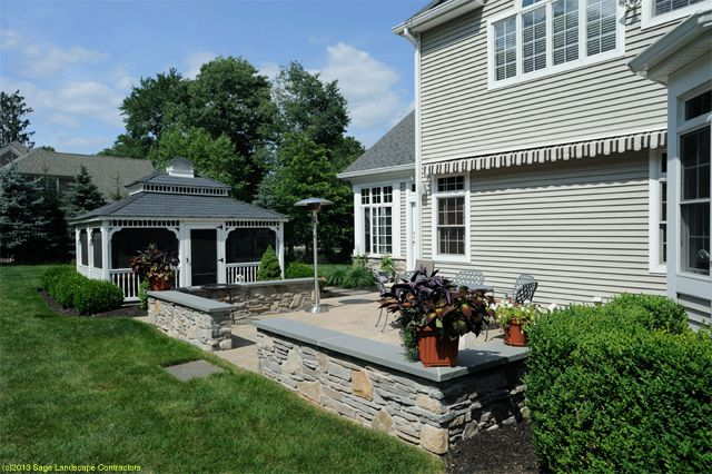 concrete patio construction with stone sitting wall and