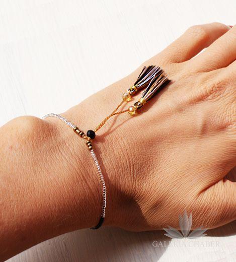 Bransoletka w stylu boho wykonana z mocnego, delikatnego sznurka i kryształków oraz koralików w kolorach złotym, czarnym i beżowym. Dodatkowo możliwość regulacji długości. Sznureczek dodatkowo ozdobiony frędzelkami z miękkiej bawełny.