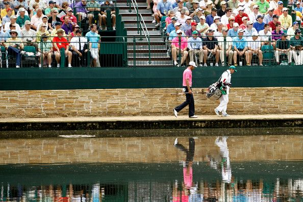 Alvaro Quiros of Spain and his caddie Michael Kerr walk over the Sarazen Bridge to the 15th green during the first round of the 2012 Masters Tournament