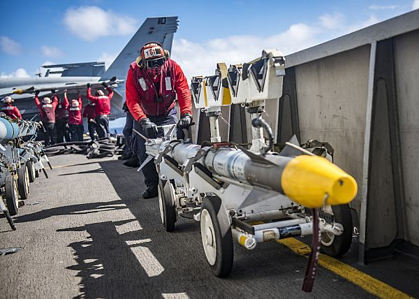 Aviation Ordnanceman Airman Charles Joseph transports a missile on the flight deck of the Nimitz-class aircraft carrier USS Carl Vinson (CVN 70).