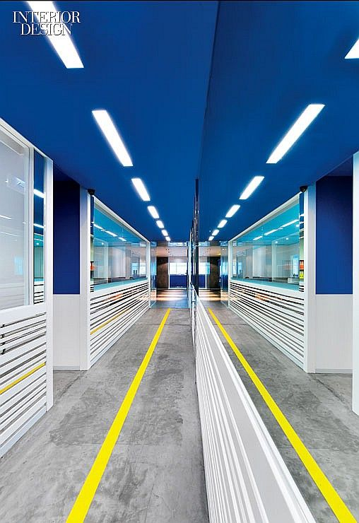 Speed mark office design in Hong Kong designed by Joey Ho Design. Flooring in the central corridor is raw concrete, emblazoned with a yellow stripe to simulate a runway. #office: