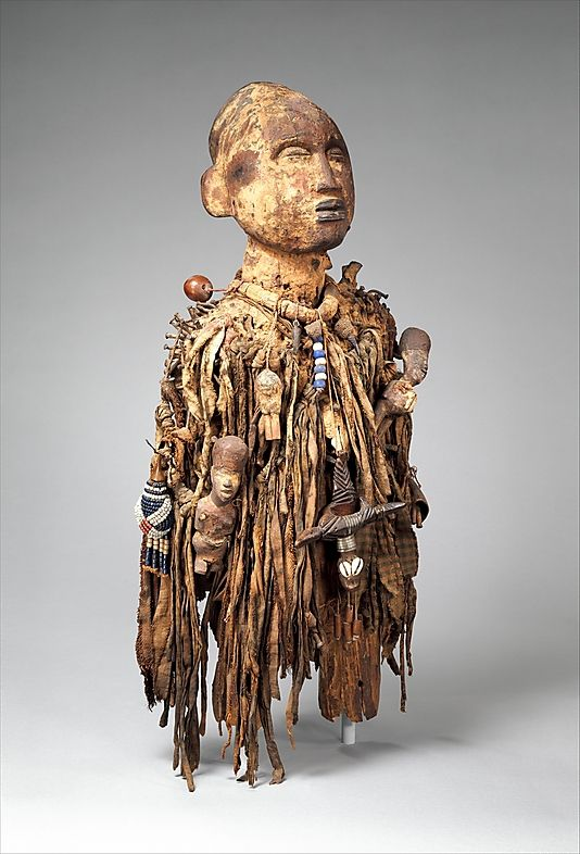 Power Figure: Male (Nkisi) Date: 19th–mid-20th century Geography: Democratic Republic of the Congo Culture: Kongo peoples Medium: Wood, pigment, nails, cloth, beads, shells, arrows, leather, nuts, twine Dimensions: H. 23 1/8 x D. 10 1/4 x W. 10 in. (58.8 x 26 x 25.4 cm) Classification: Wood-Sculpture Cllick on link to the Met to read all of the info about this.