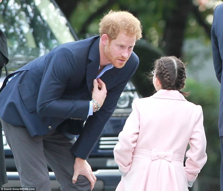 Prince Harry leans over to chat to a wellwisher as he arrives at London's County Hall with William and Kate