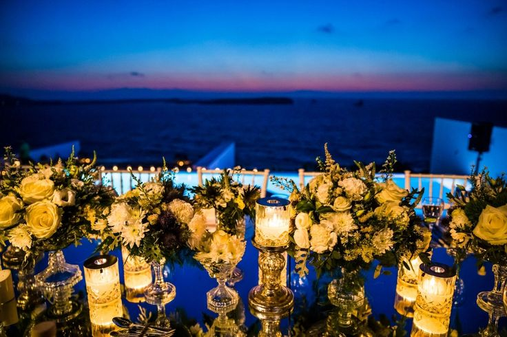 Crystal candles, white and green flower compositions and the view of the Aegean Sea during sunset <3