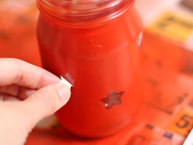 Spray paint over stickers on mason jars to create luminaries