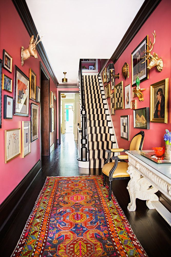 Mix a range of contrasting prints and styles to create a bold, show-stopping hallway. A Persian rug, striped staircase runner, and a cache of vintage art marry the bohemian and preppy strains of the home's aesthetics.