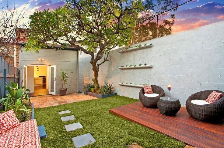 Jardim com árvore, deck de madeira e poltronas.  Fotografia: www.decorfacil.com.