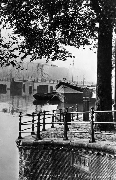 1950's. View of the river Amstel and Magere Brug (skinny bridge) in Amsterdam. The river Amstel runs through the city and ends at The IJ. The Amstel originally began where two smaller rivers, the Drecht and Kromme Mijdrecht, joined together, near town of Uithoorn. The well-known Magere Brug bridge in Amsterdam crosses the river, as do the Blauwbrug, Hoge Sluis and Berlagebrug bridges. Amstel beer is named after the river. #amsterdam #1950 #amstel
