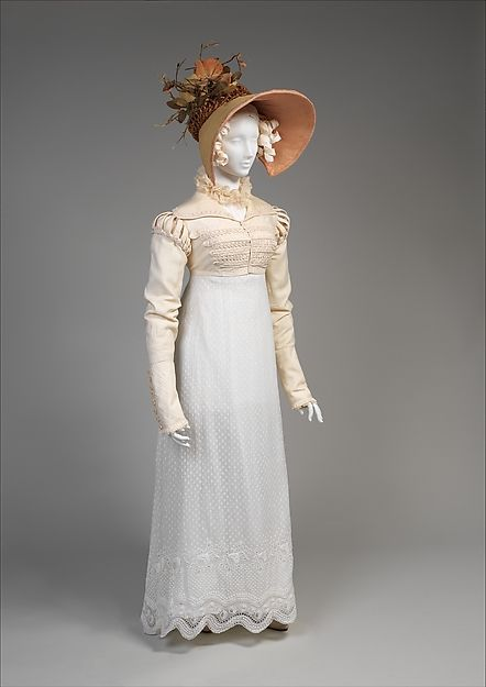 This is an excellent example of an Empire period outfit. Simple white cotton dress and a military inspired Spencer, which is the short jacket over the dress. Bonnets like the one on the mannequin were also very popular during this period. The bonnets usually were decorated with items (in this case leaves) & had wide brims called pokes.