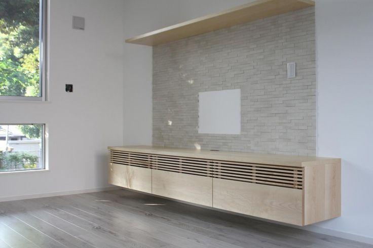 ルーバーにメープルの無垢材を使用したテレビボード。 テレビボード下には、LEDの間接照明が設置されています。