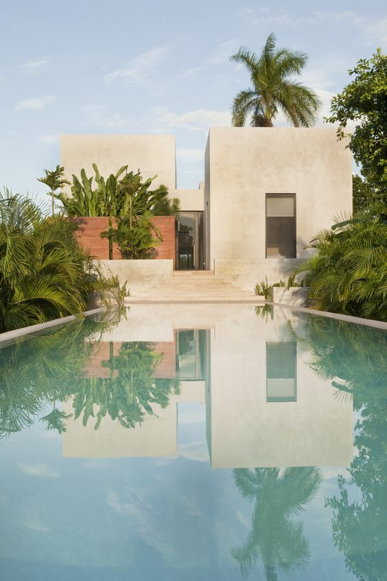 Stucco home with Bohemian features. Looks like a tropical oasis.