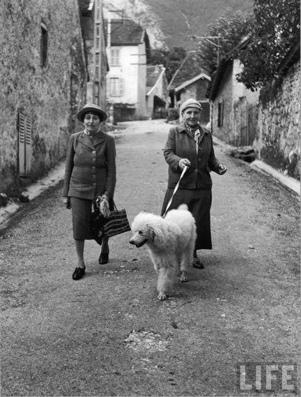 Alice B. Toklas and Gertrude Stein walking their pet poodle, Basket.  France, 1944. Carl Mydans