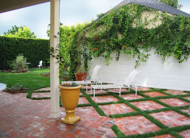 This gorgeous patio idea incorporates grass into the mix, as it's almost acting as the grout in between brick designs. If you want a completely unique concept while keeping that traditional brick work look, this is a great concept to try out. Keeping the larger slab of brick under the covered area and letting that expand out into the actual yard makes the scene great, but what is truly eye catching is that great natural grass cutting right into the design.