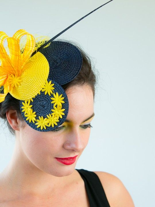"OOPS-A-DAISY | Hat/Fascinator Spring Racing Carnival | FORD MILLINERY  $375  Ring around the rosie, a beauty topped with posies! Oops-A- Daisy adds a little splash of ""cute"" to light up any outfit. Two small circular sinamay discs in navy greet one of the same in daffodil yellow. A ring of yellow posies blooms from the navy base, as the stripped turkey feather quill in navy offsets the bundled loops of golden ribbon. With a touch of yellow netting, you can play with positions to find the…"